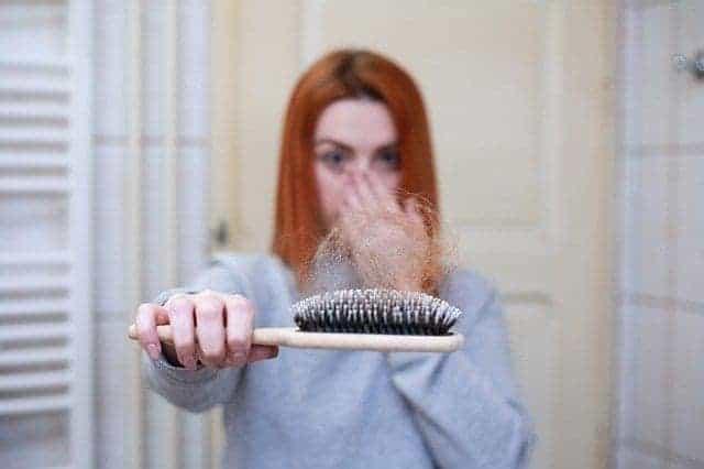 سيدة تمسك فرشاة مليئة بالشعر- أسباب تساقط الشعر